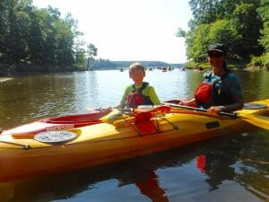 Karen Szypulski with her P&H Delphin 155 — and her son Evan (Karen bought Evan a boat not long after getting hers).
