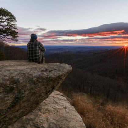 man sitting on rock watching sunset